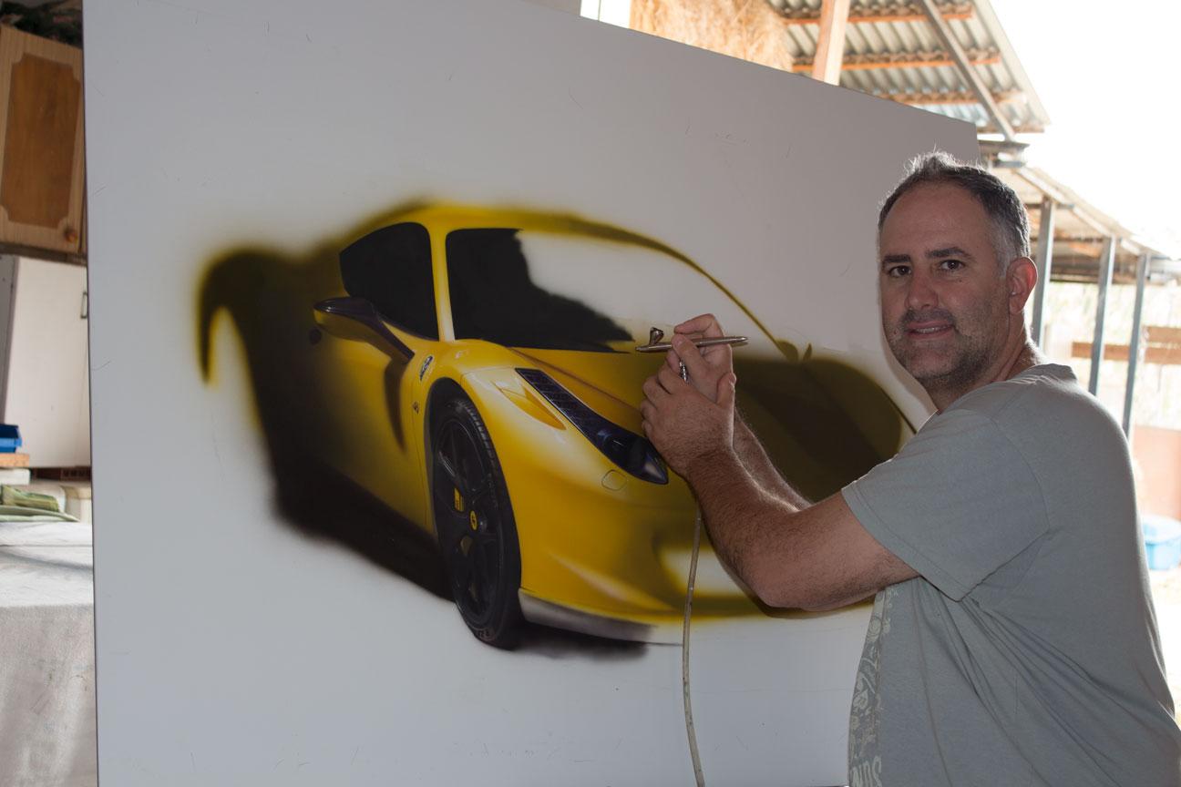 Artist Ronen Zlotogoura working on hyperrealistic painting of Ferrari