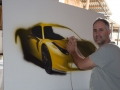 Artist Ronen Zlotogoura working on hyperrealistic painting of Ferrari
